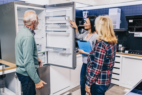 Photo Senior husband and wife, satisfied customers choosing fridges in appliances store