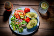 tasty avocado with green salad, tomatoes, snake cucumber, red onions and chillies