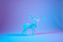 Christmas Background With White Decorative Deer On Blue Holographic Background. Banner Format, Copy Space.