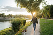 canvas print picture - Young man takes his beloved dog for a walk in the park at sunset - Millennial in a moment of relaxation with his four-legged friend