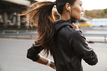 Strong fitness woman running outdoors by street.