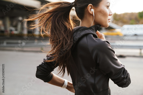 Foto Strong fitness woman running outdoors by street.
