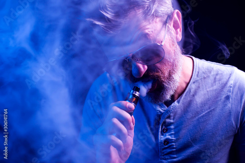 Fototapety, obrazy: Man with sunglasses smokes vape in blue background. Cigarette addiction concept