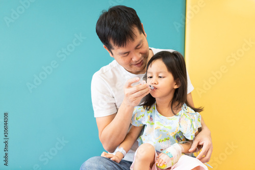 Asian father is feeding the medicine with syringe to his daughter while admit as patient in the hospital room, concept of parent care to their kid Canvas Print