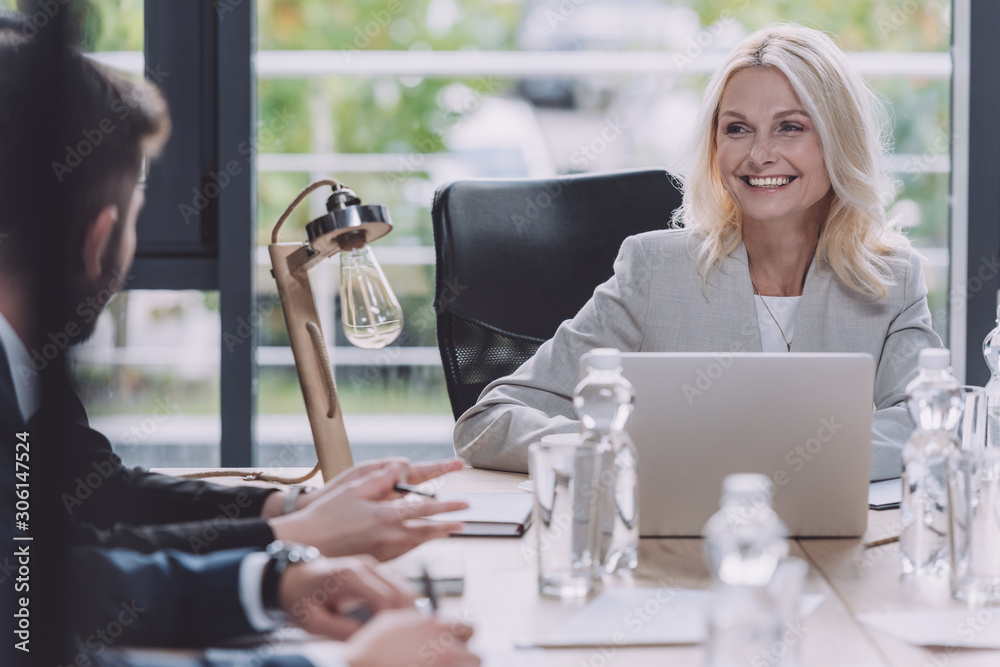 Fototapeta attractive businesswoman smiling during business meeting with young colleagues