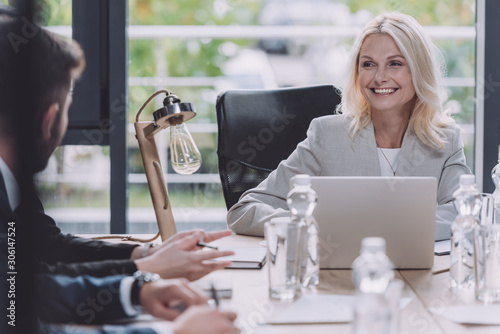 attractive businesswoman smiling during business meeting with young colleagues