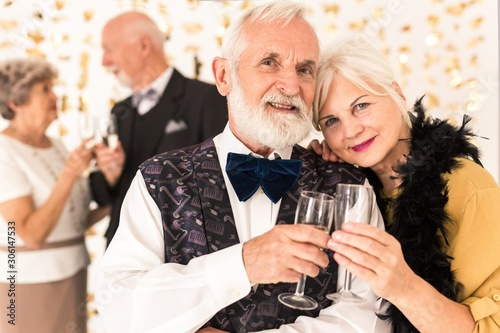 Photo Cute elegant senior couple toasting with champagne during New Year's Eve