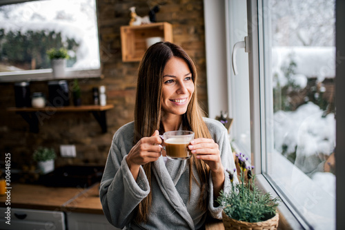 Beautiful smiling brunette looking through window and drinking coffee in the kitchen Fototapet