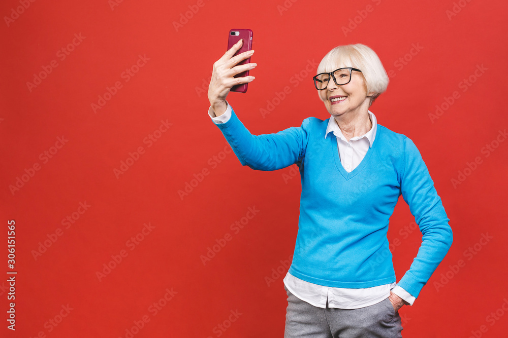 Fototapeta It's selfie time! Image of cheerful mature old woman standing isolated over red background wall talking by mobile phone.