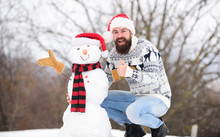 Winter Vacation. Man Made Snowman. Hipster With Beard Outdoors. Man With Santa Hat Having Fun Outdoors. Guy Happy Face Snowy Nature Background. Winter Games. Winter Activity. Fun And Entertainment
