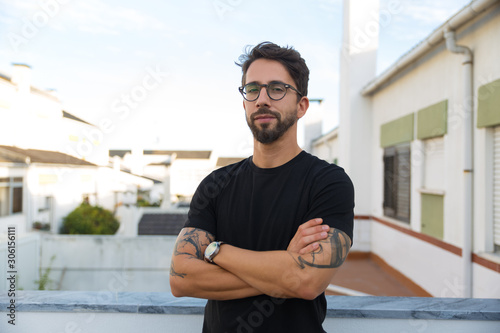 Obraz Confident stylish guy with tattoos posing on apartment balcony or terrace. Young man in glasses standing outside with arms crossed and looking at camera. Male portrait concept - fototapety do salonu