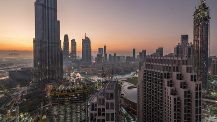 Panoramic skyline view of Dubai downtown before sunrise with mall, fountains and skyscrapers aerial night to day timelapse