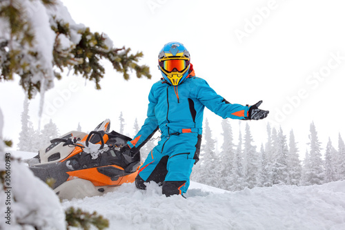 Photo  Ryder stands next to the fallen snowmobile and spreads his hands