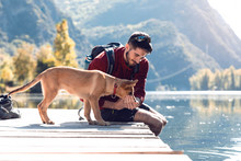 Young Traveler Hiker With Backpack Giving Water To Dog On The Lake.