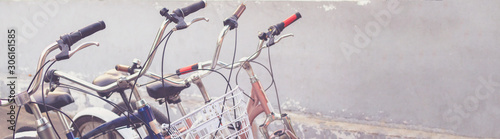 Fototapeta Old retro cruisers bicycles near a gray wall. Steering wheel, tire, cliffs, seat, mirror and lock are visible. selective soft focus. obraz