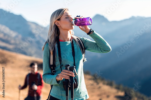 Obraz Pretty young woman traveler with backpack drinking water while standing on mountain. - fototapety do salonu