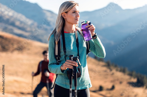 Fotografiet Pretty young woman traveler with backpack looking to the side while drinking water on mountain