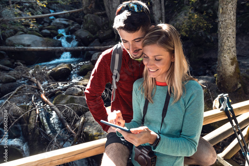 Two travel hikers doing a consultation with your mobile phone on the wood bridge in the forest Fototapete