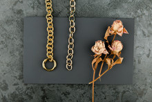Gold Chain On A Dark Background. Decorated With Dried Roses. Handwork.