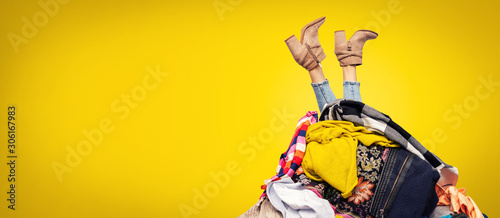 Fototapeta woman legs out of clothes pile on yellow background with copy space obraz