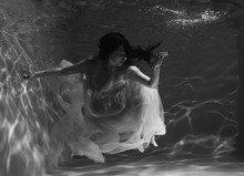 A Girl With Long Dark Hair Swims Underwater In A Pink Dress And With A Crown On Her Head, Like An Underwater Queen. Fairy Tale Suitable For Advertising
