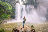 Young blond woman standing on a rock watching the landscape with a waterfall in the middle of the jungle