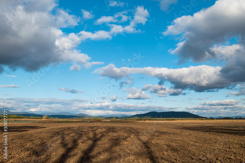 Ploughed field under cloudy sky Canvas Print