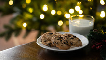Christmas Concept - Cookies And Milk Left For Santa Claus, In Front Of Christmas Lights, Bokeh