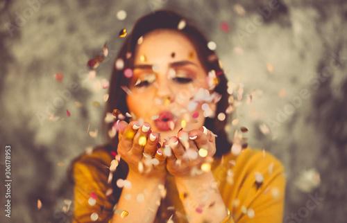 Obraz Happy beautiful brunette girl wearing yellow sweater blowing on confetti - fototapety do salonu