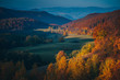 Amazing dawn autumn scenery with colorful trees on meadow, fog above valley and mountain ranges on background. National Natural Park Synevir, the Carpathian Mountains,