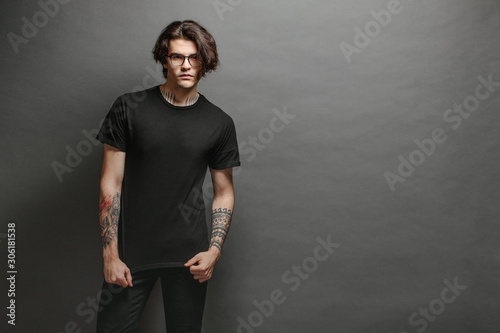 Obraz Hipster handsome male model with glasses wearing black blank t-shirt and black jeans with space for your logo or design in casual urban style - fototapety do salonu