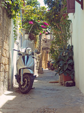 A Scooter Parked In A Narrow T...