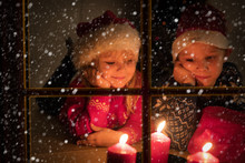 Little Boy And Girl Looking At Christmas Candles Viewed From Outside Window