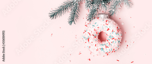 Christmas toy donut with sugar sprinkling hanging on Christmas tree branch, banner format