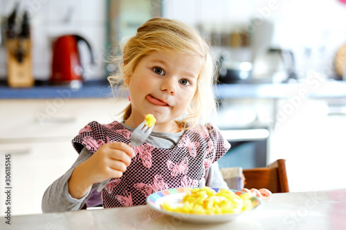 Photo Lovely toddler girl eating healthy fried potatoes for lunch