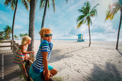 happy boy and girl looking at tropical beach with palms Canvas Print