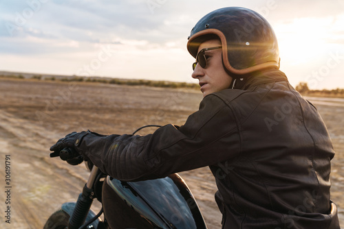 Tablou Canvas Young man biker on bike outdoors at the desert field.