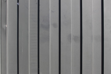 Gray metal gate with vertical lines closeup