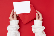 Women's Hands Holding An Empty Postcard And Red Envelope On The Red Background. Christmas Concept
