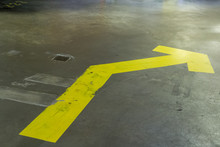 Yellow Bent Sign On The Floor Pointing Towards The Garage Door Exit One Way System To Control Traffic In The Indoor Car Parking Area Public Controlling And Health And Safety Of Organised Car Driving
