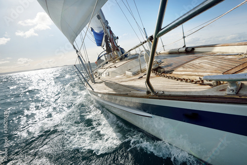 Fotografia Sloop-rigged modern yacht with wooden teak deck sailing on a clear day