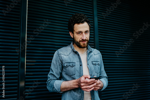 Half length portrait of handsome caucasian man holding mobile phone standing on street in casual wear, hipster guy typing message on modern smartphone chatting online via 4G internet connection Fototapet