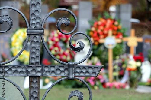 Fotomural Am Friedhof, Im Vordergrund ein schmiedeeisernes Grabkreuz, im unscharfen Hinter