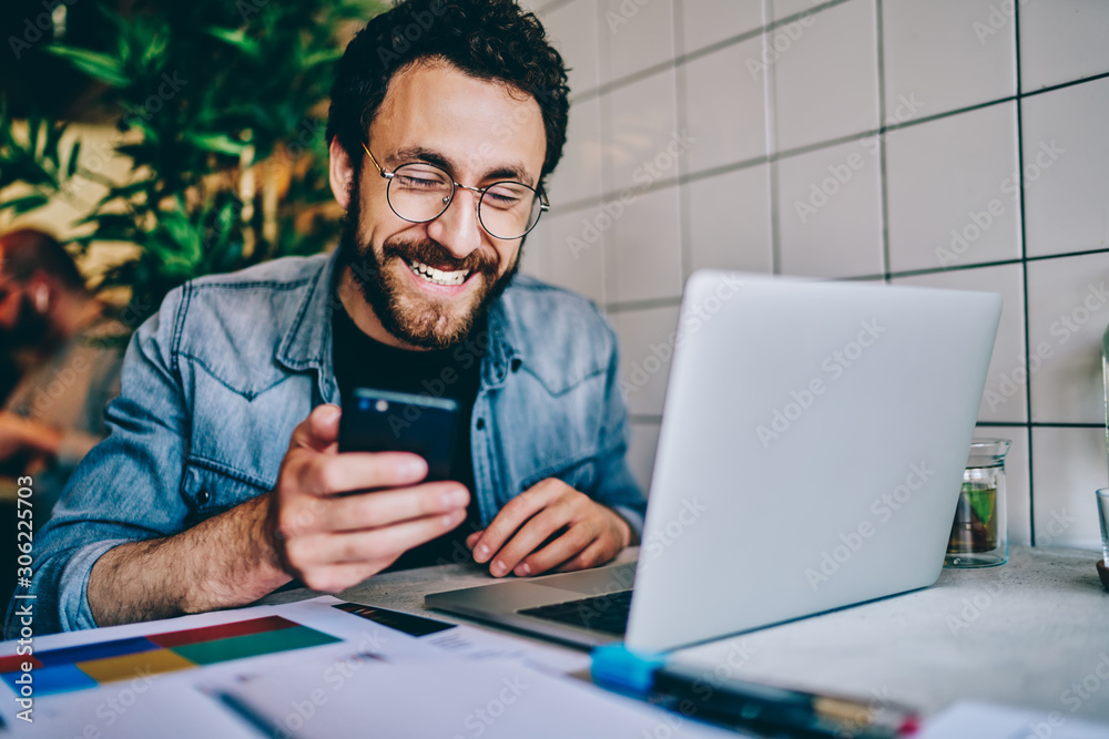 Fototapeta Positive caucasian hipster guy in eyewear laughing at content from social networks using mobile phone for browsing, cheerful male freelancer having fun during remote job  chatting on cellular.