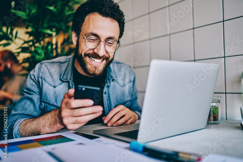 Fototapeta Positive caucasian hipster guy in eyewear laughing at content from social networks using mobile phone for browsing, cheerful male freelancer having fun during remote job  chatting on cellular. obraz