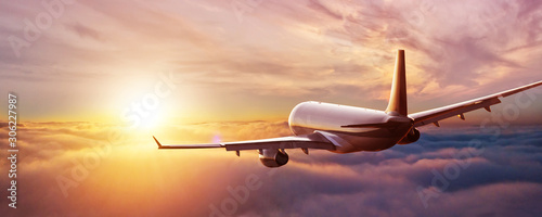 Passengers commercial airplane flying above clouds Canvas Print