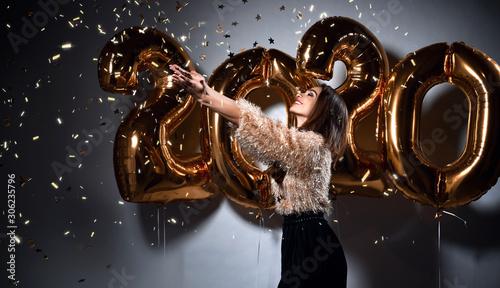 Fotografia  Beautiful woman celebrating New Year with gold 2020 balloons