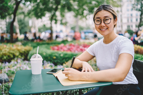 Valokuva Half length portrait of attractive smiling smart female author in glasses for better vision pondering about ideas for publication