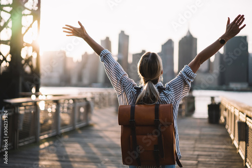 Back view of accomplished tourist woman with trendy backpack and raised hands ce Canvas Print