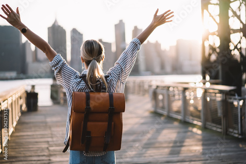 Back view of accomplished tourist woman with trendy backpack and raised hands celebrating win with trip to American city - New York, female traveller complete triumph and win goal during journey #306237537